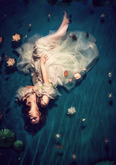 An editorial fashion shot of a female model posing indoors in water - fashion photography types