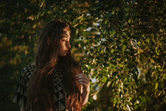Atmospheric self portrait of a female model posing outdoors surrounded by trees - fine art photography mistakes