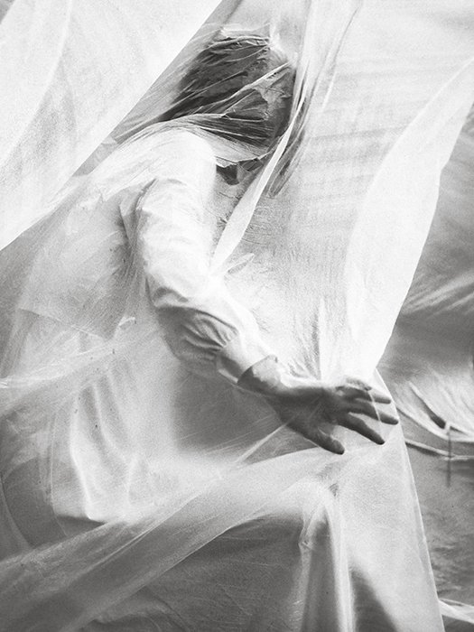 Conceptual fine art portrait of a female model covered in material, shot in black and white
