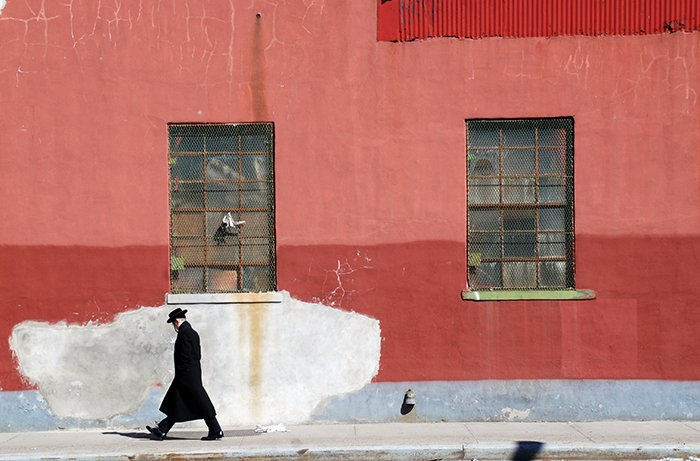 A fine art photo of a man walking down the street past a red wall