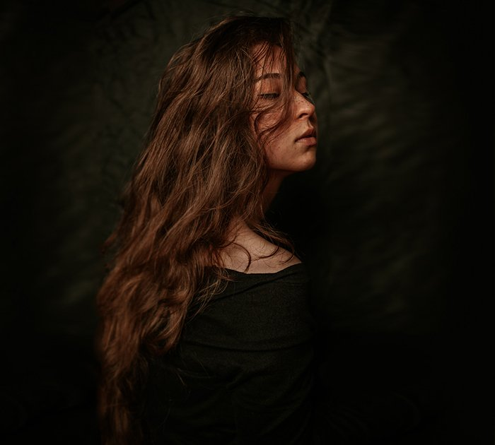 Atmospheric self portrait of a female model posing against a black background - fine art photography mistakes