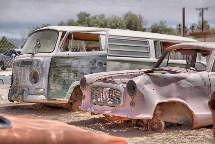 A photo of rusty broken down cars in a junkyard - fix bad photography