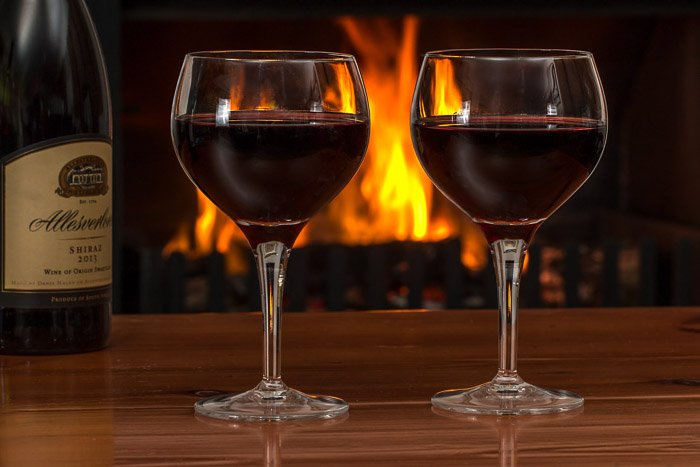 A photo of a bottle of wine and two glasses with a fire in the background