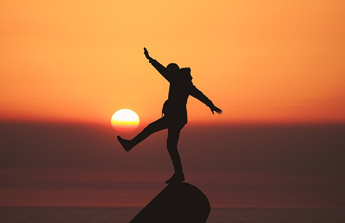 The silhouette of a person balancing on a pink in front of a beautiful sunset