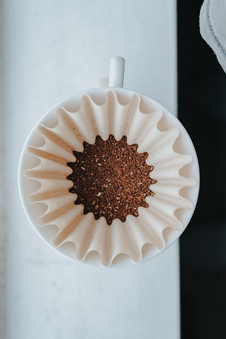 An overhead shot of a coffee filter filled with coffee grounds - Gestalt Theory photography