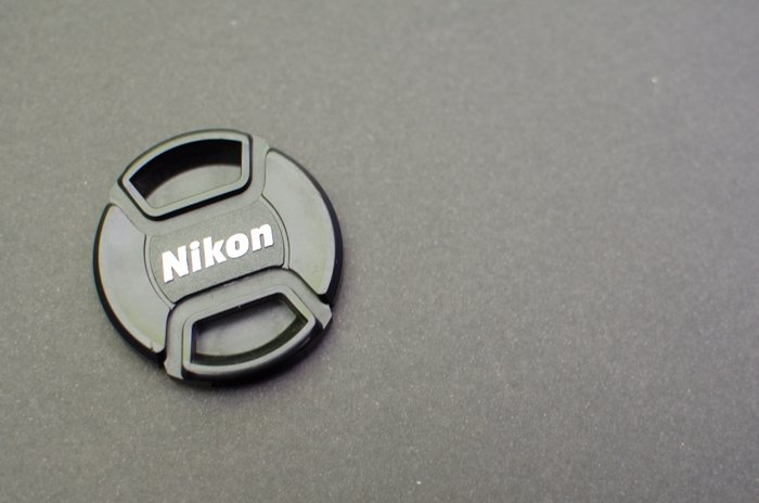 A Nikon lens cap on grey background - grey card photography