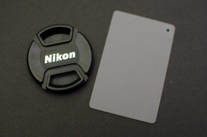 A Nikon lens cap on grey background with a photography grey card beside it