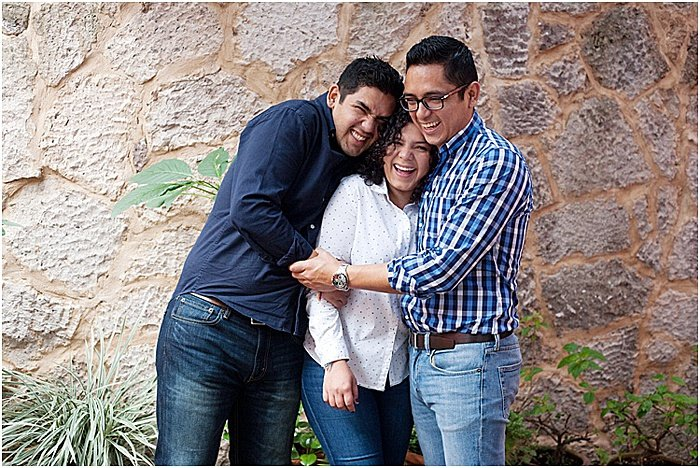 Three friends smiling, laughing and embracing posing outdoors - emotional photography