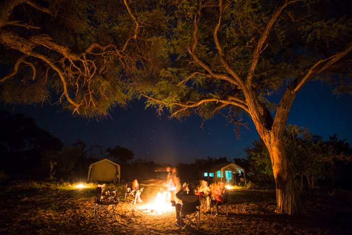 People sitting around a campfire at night during a safari photography trip