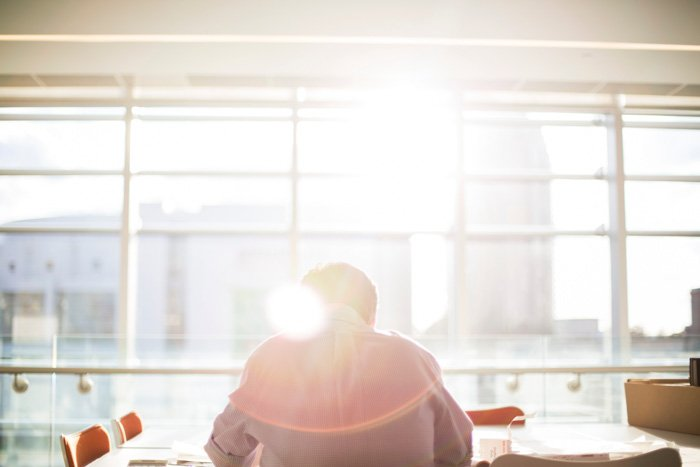 A photo of a man working in an office, with a creative lens flare effects coming from the window above his head