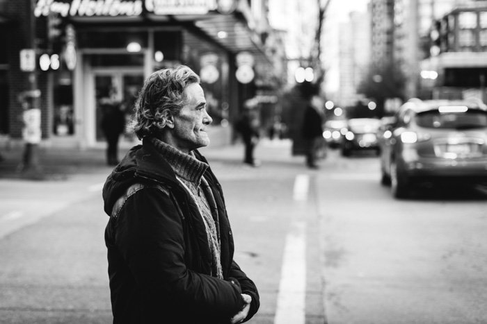 A black and white street photography portrait of a man crossing a road shot using manual focus mode