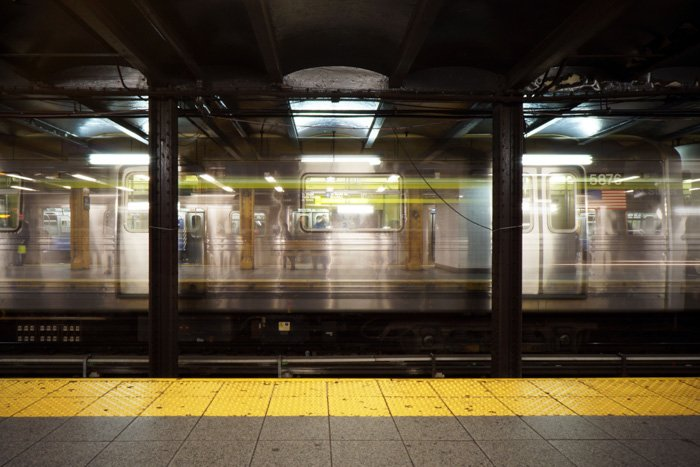 Atmospheric long exposure photo of a subway train moving through a station shot using manual focus