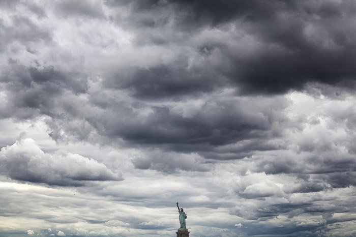 The statue of liberty under a cloudy sky - minimal landscape photography