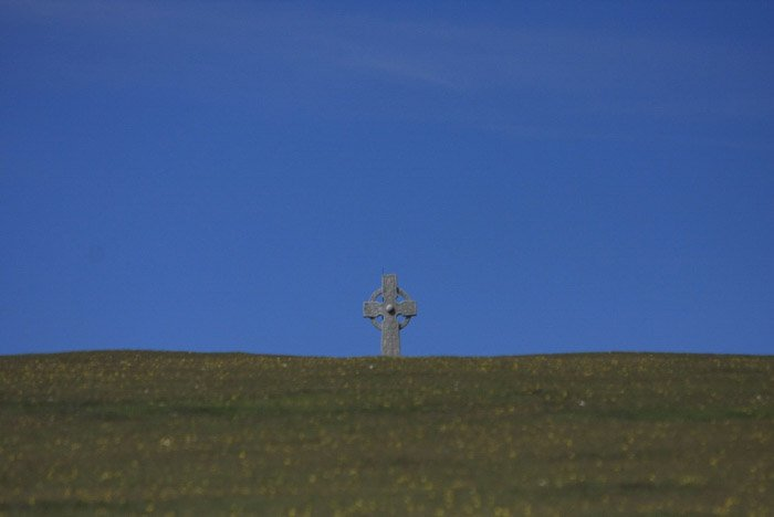 A minimalist landscape photography shot featuring a stone cross under a clear blue sky