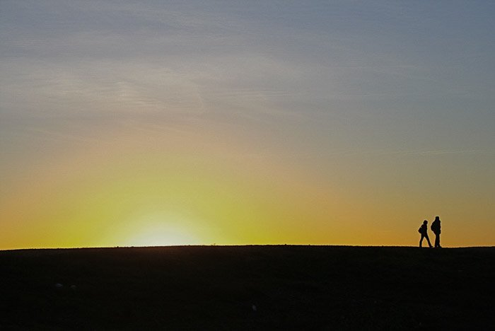 Silhouettes of two people walking through a minimalist landscape at sunset
