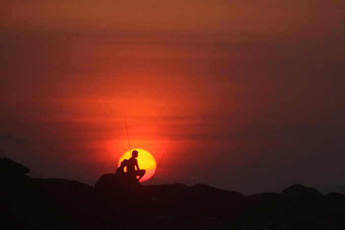 Silhouettes of two people sitting on rocks sunset - minimalist nature photography