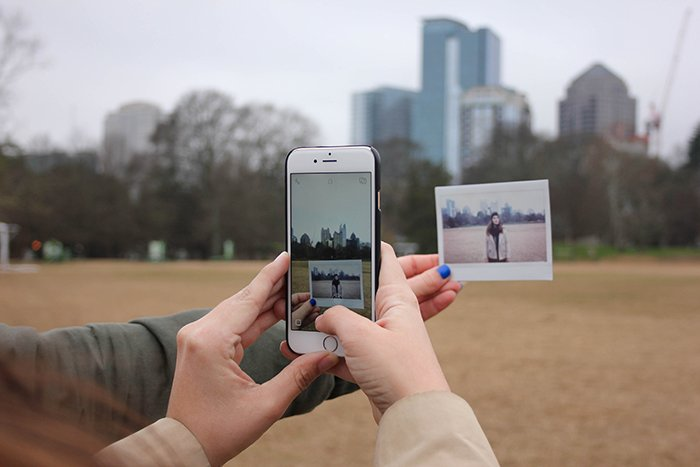 Close up shot of a person taking a photo of a printed polaroid with a smartphone