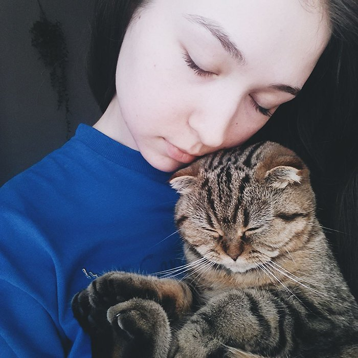 A sweet portrait of a female model posing with a tabby cat - smartphone pet photography