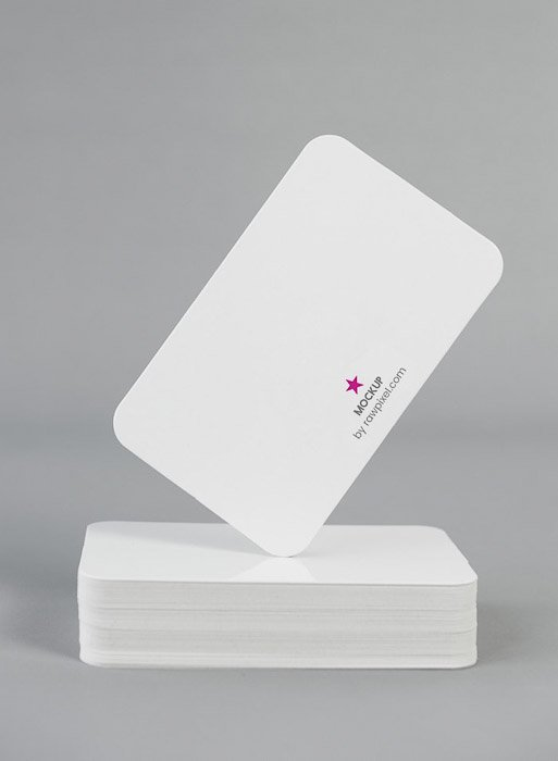 A stack of white photography business cards with a minimalist logo printed on them