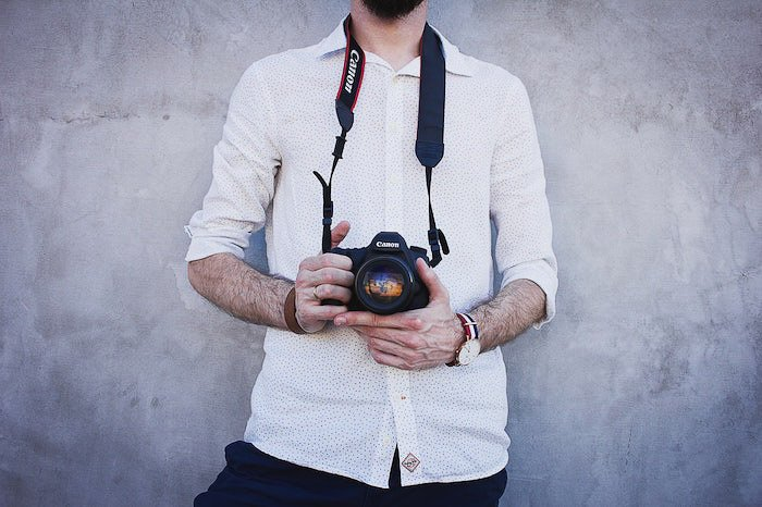 an image of a photographer holding a Canon DSLR camera standing against a grey wall