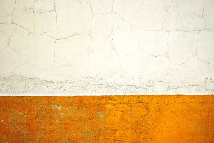 A simple and effective example of abstract photography of a cracked white and yellow wall