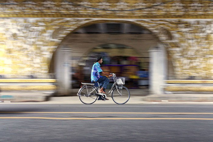 A cyclist passing under the bridge with creative motion blur using slow shutter speed