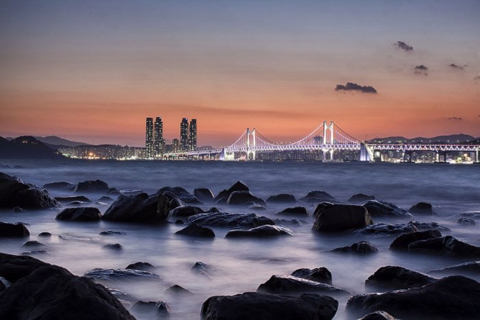 A rocky coastline in the foreground of a coastal cityscape at sunset shot with slow shutter speed