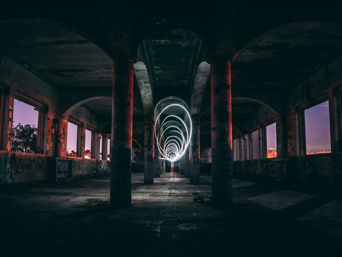 Light painting in an abandoned industrial interior at night using slow shutter speed