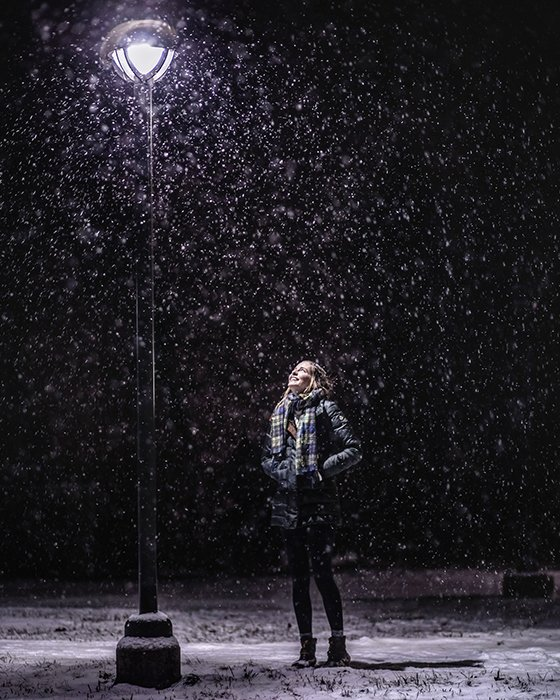 Atmospher winter portrait of a female model posing under falling snow at night