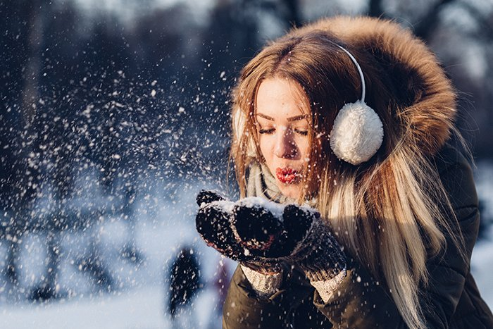 Close up winter portrait photography of a female model posing playfully in the falling snow