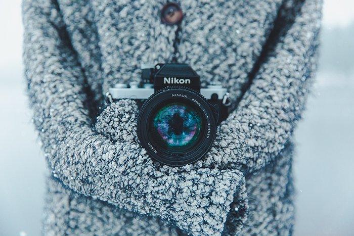 A close up of a Nikon camera around the neck of a photographer, shooting snow portraits