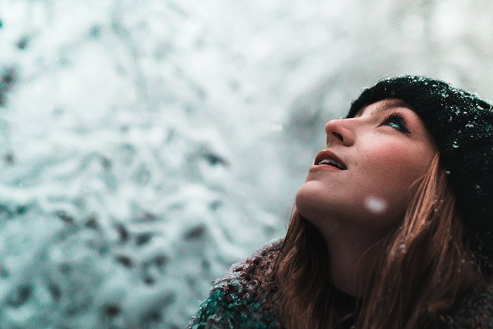 Close up winter portrait photography of a female model posing in the falling snow