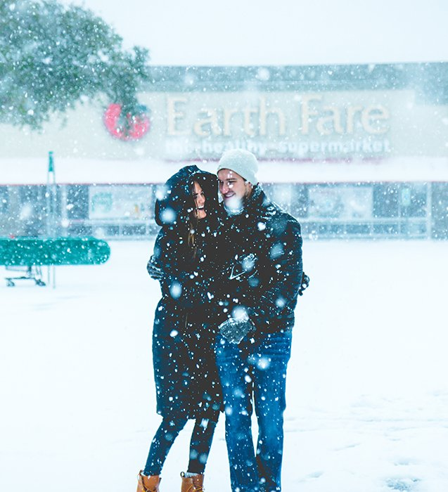 Close up winter portrait photography of a couple posing in the falling snow