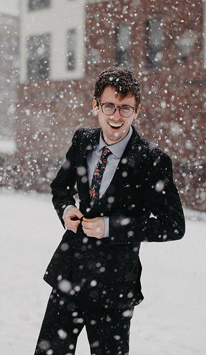 Fun winter portrait of a male model posing casually under falling snow