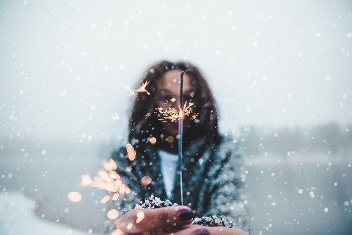 Atmospher winter portrait of a female model posing with sparklers under falling snow at night