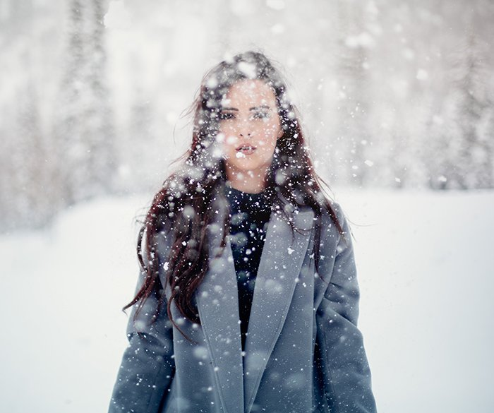 Magical winter portrait photography shot of a female model posing in the falling snow