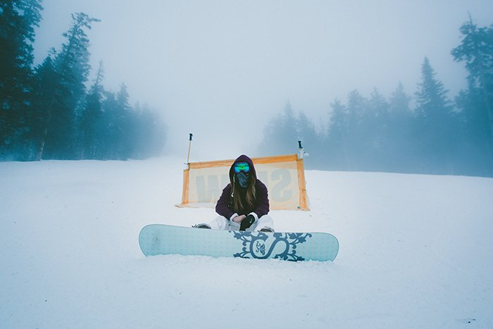 Atmospheric snow portraits of a female snowboarder posing in a winter landscape