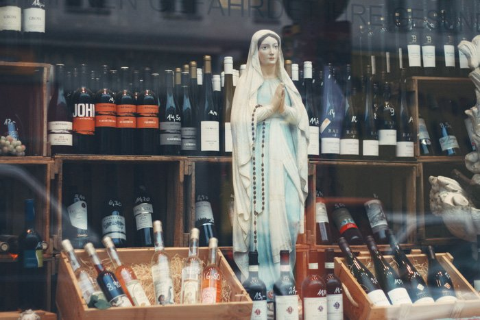 A statue of the virgin Mary in an alcohol shop window, shot using a standard lens