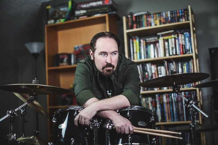 A portrait of a man posing by a drum kit - types of photography lighting