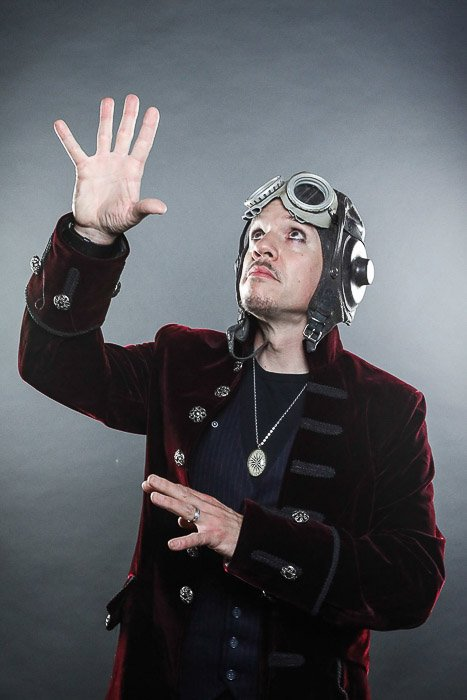 A studio portrait of a male model wearing an aviator hat and red velvet jacket - photography light bulbs