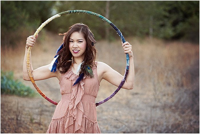 A teenage girl posing outdoors with a hula hoop