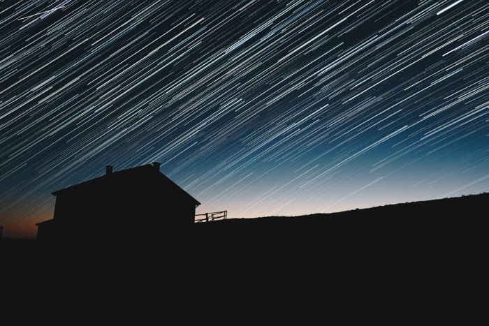 A stunning star filled sky over the silhouette of a house