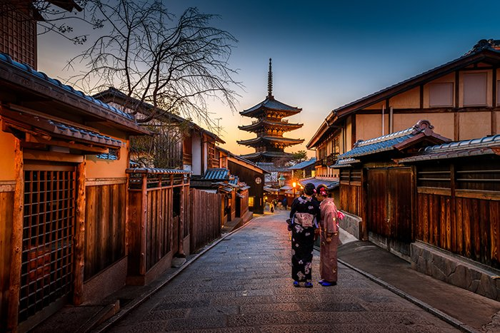 A portrait of two people standing by an impressive temple in Kyoto at sunset - pictures of Japan