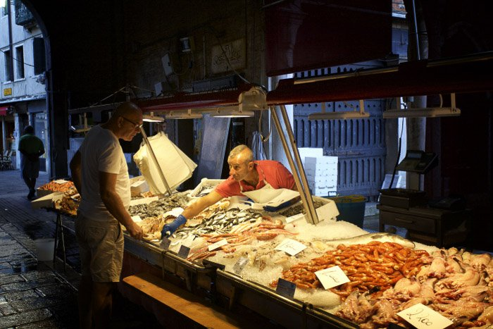 A man interacting with a market vendor at a fish market in Venice - Italy pictures