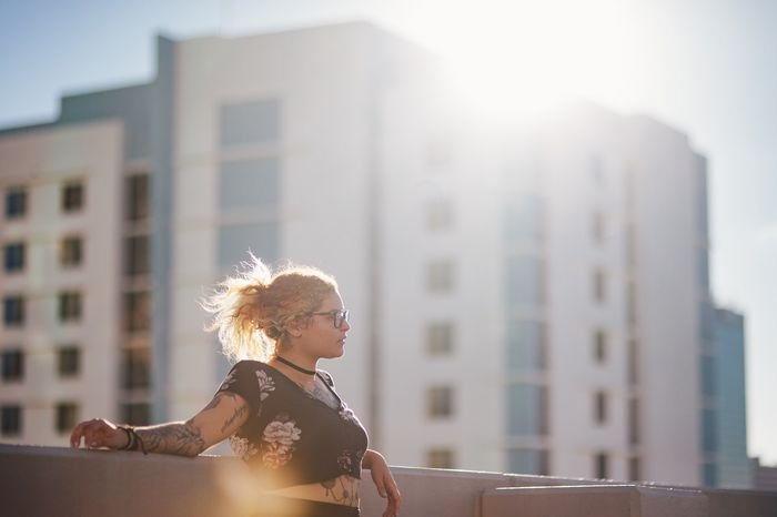 photo of a girl on top of a building with lens flare