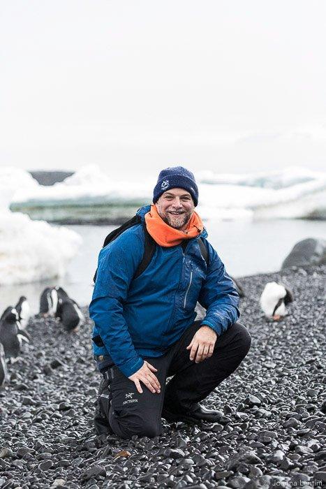A wildlife photographer sitting on a beach amid penguins - wildlife clothes
