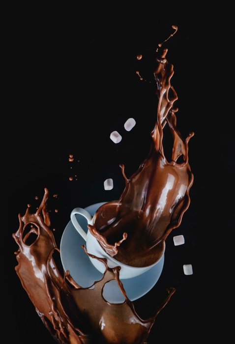 A creative shot of a falling coffee cup mid splash