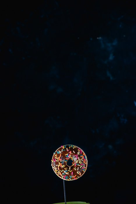 A donut on dark background - setup for creating chocolate splash photography