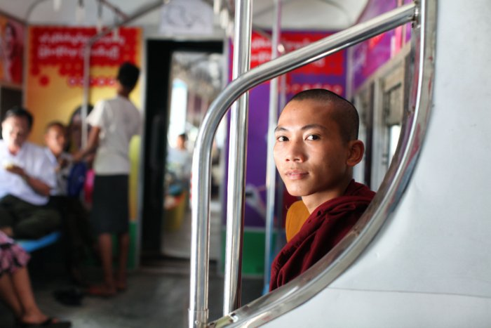 Portrait of a Buddhist monk sitting in the interior of a train