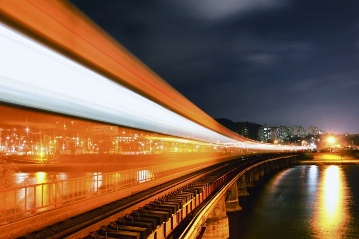 Colorful orange and white light trails moving over train tracks